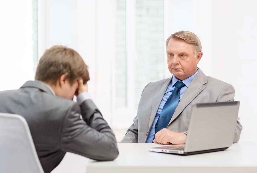 business, technology and office concept - older man and young man having argument in office